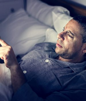 man-using-phone-on-a-bed-DE87TVN (1)